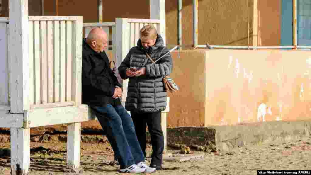 Пожилые люди греются на солнце