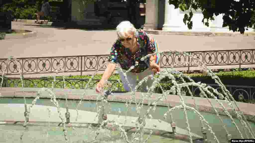 Женщина мочит руки в прохладной воде фонтана