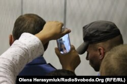 Правозахисниця намагається зняти на камеру підозрюваного Богдана Тицького, який лежить непритомний у залі суду. Кордон правоохоронців не дозволяє знімати затриманого