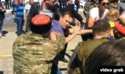 Russian opposition leader Aleksei Navalny (in purple shirt) and his supporters are attacked by Cossacks in Anapa in 2016.