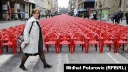 Женщина проходит мимо красных стульев, число стульев 11 541 символизирует число погибших. Сараево, 6 апреля 2012 года.