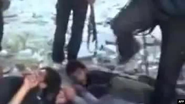 A video dated November 1 uploaded on YouTube appears to show Syrian government forces lying on the ground and being kicked before being shot by rebel fighters at the Hamisho checkpoint near Saraqeb.