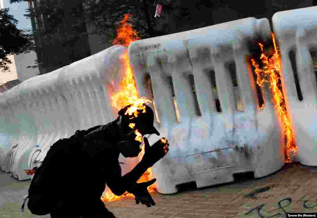An anti-government protester catches fire after throwing a Molotov cocktail during a demonstration in Hong Kong. (Reuters/Tyrone Siu)