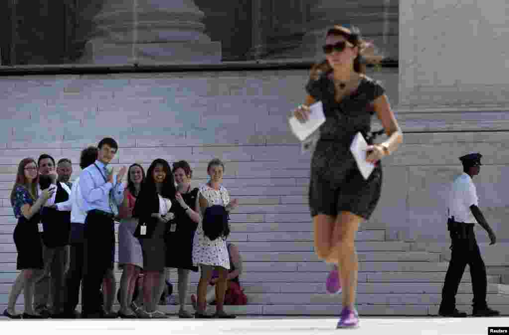 Onlookers applaud as a news assistant sprints out of the Supreme Court to deliver copies of the court's rulings to news crews outside the court building in Washington. (Reuters/Jonathan Ernst)