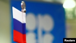 The Russian flag and the OPEC logo are seen at a news conference in Vienna, where the oil cartel is meeting with Russia and other non-OPEC producers about an output cut.