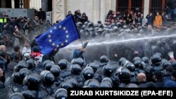 Riot police disperse opposition supporters during a protest rally in front of the parliament building in Tbilisi on November 18.