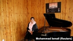Maram Atayee, 16, a pianist at the Afghan National Institute of Music poses for a picture in Kabul.
