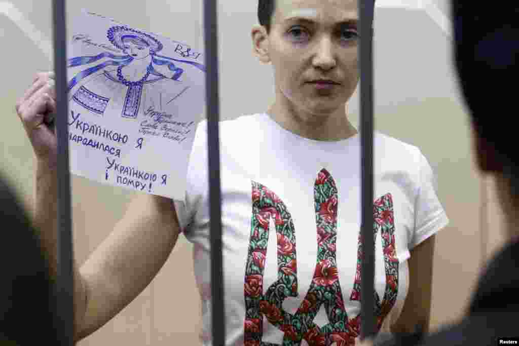 "Jailed Ukrainian army pilot Nadia Savchenko holds a sign inside a defendants' cage as she attends a hearing at a court in Moscow on February 10. Savchenko has been on hunger strike, protesting her incarceration, for eight weeks. The sign she is holding says: ""I was born Ukrainian; I will die Ukrainian."" (Reuters/Maxim Zmeyev)"