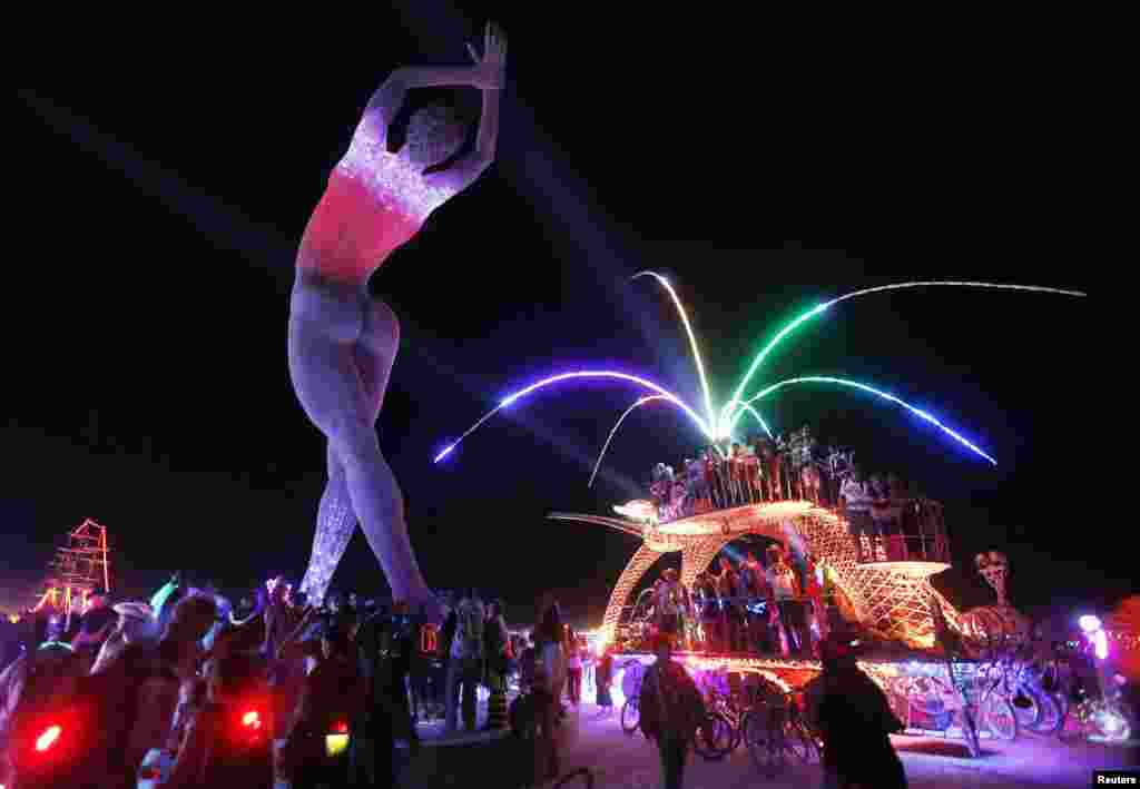 "Participants dance on top of a car parked beside the ""Truth is Beauty"" sculpture, created by Marco Cochrane, at the Burning Man arts and music festival in Nevada."