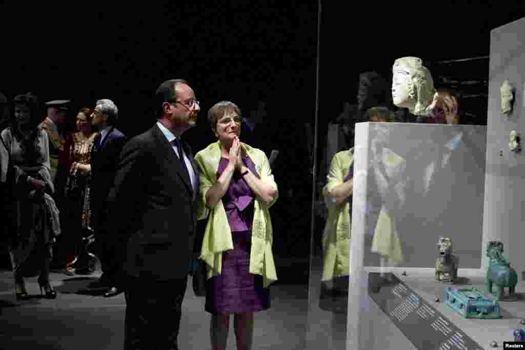 French President Francois Hollande listens to Sophie Makariou, the head of the Islamic Arts Department.