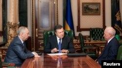 Виктор Янукович (в центре) и Николай Азаров (справа) в бытность президентом и премьером Украины. Киев, 23 декабря 2013 года.