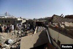 Местные жители смотрят на руины на месте воздушного налета вблизи аэропорта в городе Сана. 31 марта 2015 года.