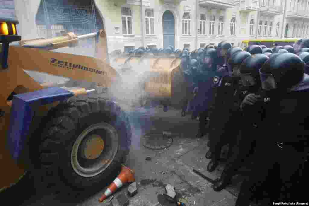 Protesters brought a tractor to try to break through police lines near the presidential administration building in Kyiv.