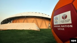 Катар - Мяч с логотипом МЧ-2022 на фоне построенного по современным технологиям стадиона в Дохе