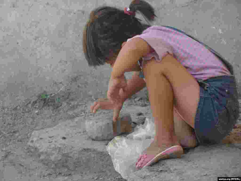 Девочка во дворе общежития пытается расколоть косточку абрикоса.