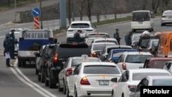 Armenia -- Police officers enforcing a coronavirus lockdown check cars leaving Yerevan, April 1, 2020.