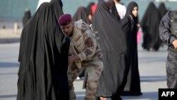 Бағдад қаласына барар жолда полицей әйелді тексеріп жатыр. 6 қазан 2013 жыл.