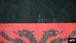 Një pjesëtar i forcave speciale të Shqipërisë, qëndron pranë një flamuri të vendosur në stadiumin e Elbasanit. Foto ilustrim.