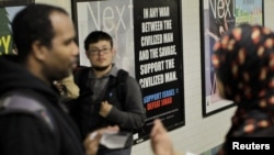 "Members of the Council on American-Islamic Relations talk with commuters near an advertisement that reads ""Support Israel/Defeat Jihad"" in the Times Square subway station in New York last month."