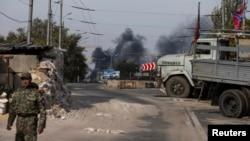 Бойовик угруповання «ДНР» на фоні диму, який піднімається над Донецьким аеропортом після обстрілу, 23 вересня 2014 року