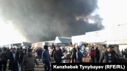 Люди идут по дороге рядом с горящим рынком. Алматы, 17 ноября 2013 года.