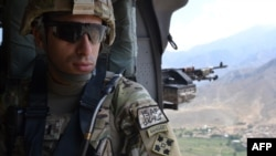 "Captain Florent A. ""Flo"" Groberg enjoys the view from a UH-60 Black Hawk helicopter traveling over the Kunar province in 2012."