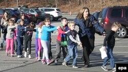 Сэнди Хук мектебінің мұғалімдері оқушыларын мектептен әкетіп барады. АҚШ, Ньютаун қаласы, 15 желтоқсан 2012 жыл.