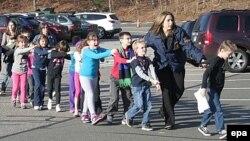Полиција ги евакуира децата по нападот во основно училиште во Њутон на 14 декември.