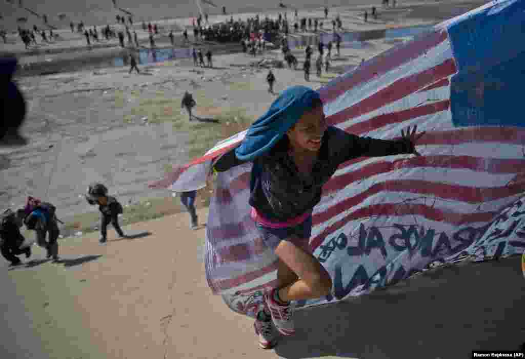 A migrant woman helps carry a handmade U.S. flag up the riverbank at the Mexico-U.S. border after getting past Mexican police at the Chaparral border crossing in Tijuana as a group of migrants tried to reach the United States. (AP/Ramon Espinosa)