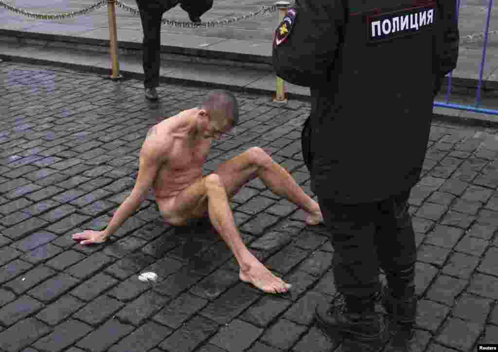 Moscow police approach artist Pyotr Pavlensky on Red Square after he nailed himself to the pavestones by his genitals as part of an art performance in protest of what he sees as apathy in contemporary Russian society and the possibility such indifference can lead eventually to a police state. (Reuters/Maksim Zmeyev)