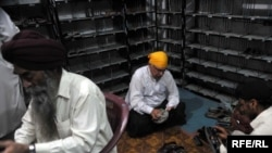 Khurshid Khan (in yellow head-covering) shining shoes to help show brotherhood with the Sikh community in Peshawar.