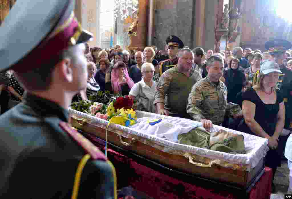 People take part in the funeral ceremony for opera singer Vasyl Slipak, who died fighting Russia-backed forces in eastern Ukraine, in St. Paul and Peter Cathedral in the western city of Lviv on July 1. (AFP/Yuriy Dyachyshyn)