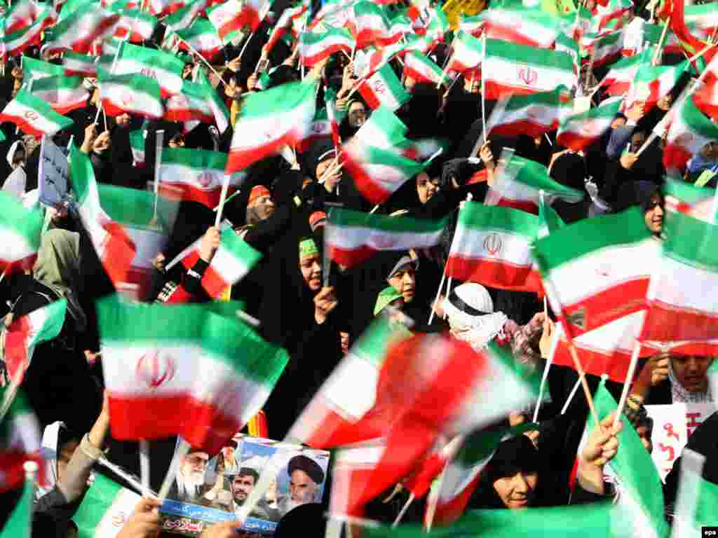 Female students in Tehran wave national flags during a ceremony marking the anniversary of the Islamic Revolution.