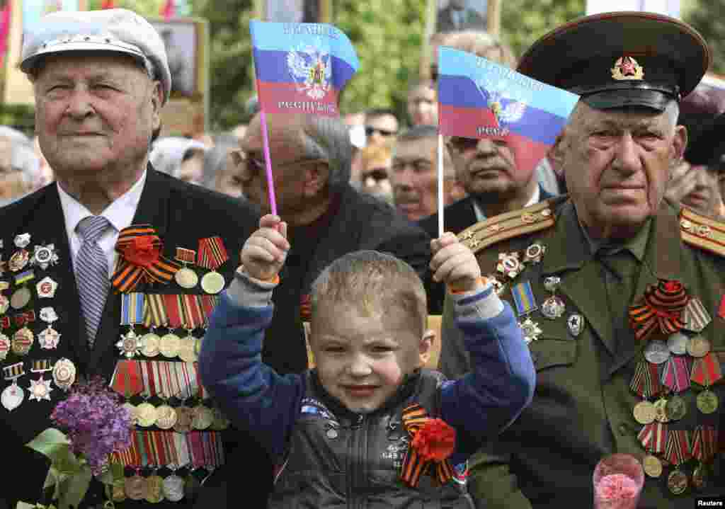 """A child holds flags saying """"Luhansk Republic"""" as he celebrates Victory Day with former Soviet servicemen during celebrations in the eastern Ukrainian city of Luhansk on May 9. (Reuters/Valentyn Ogirenko)"""