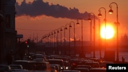 Russia -- Pipes of a thermal power plant are seen during sunset, with cars stuck in a traffic jam in the foreground, in St. Petersburg, 15Feb2011
