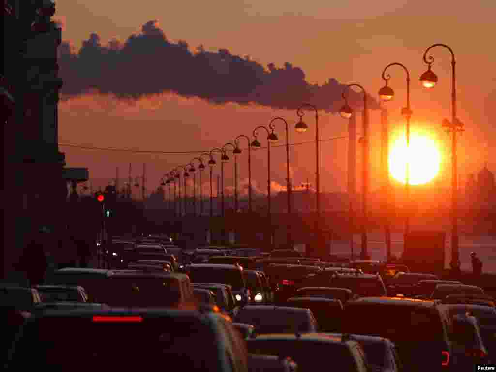 Pipes of a thermal power plant are seen during sunset, with cars stuck in a traffic jam in the foreground, in St. Petersburg on February 15.Photo by Aleksandr Demianchuk for Reuters