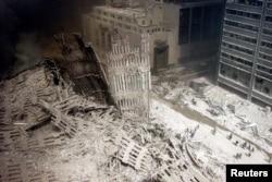 Un grup de pompieri se plimbă printre dărâmături în apropierea bazei unuia din turnurile gemene, distruse la data de 11 septembrie 2001. În cel mai grav atac terorist petrecut vreodată în Statele Unite, două avioane deturnate s-au izbit de cele două turnuri ale complexului World Trade Center din New York. Un al treilea avion a lovit Pentagonul, iar un al patrulea s-a prăbușit pe un câmp din statul american Pennsylvania.