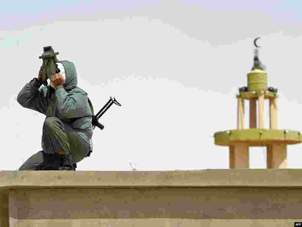 Лівійський повстанець оглядає пустелю за 40 кілометрів від портового міста Бреґа, 6 квітня. Photo by Odd Andersen for AFP