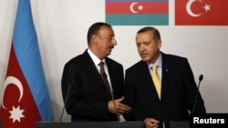 Turkey -- Azerbaijan's President Ilham Aliyev (L) chats with Turkey's Prime Minister Tayyip Erdogan during a news conference following a signing ceremony in Istanbul, 26Jun2012
