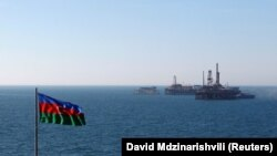 Государственный флаг Азербайджана на фоне нефтебуровых установок на Каспии.