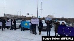Группа активистов с флагами Казахстана и ЕС и плакатом с призывом освободить политических заключенных на акции протеста у представительства Европейского союза. Нур-Султан, 26 ноября 2019 года.