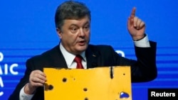 Ukrainian President Petro Poroshenko holds a fragment of a bus body that he says shows a Russian missile attack on a civilian bus as he addresses The Future of Ukraine event in the Swiss mountain resort of Davos on January 21.