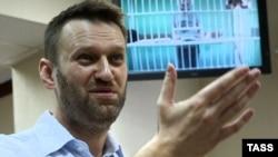 Alexei Navalnî în instanța de judecată de la Moscova, pe fundal - fratele său Oleg Navalnî din închisoare, 17 februarie