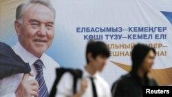 Молодые люди проходят мимо билборда с изображением президента Казахстана Нурсултана Назарбаева. Алматы, 22 февраля 2011 года.