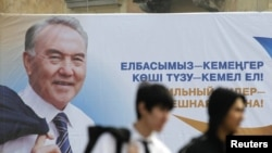 Men walk past an election poster of Kazakh President Nursultan Nazarbaev in Almaty.