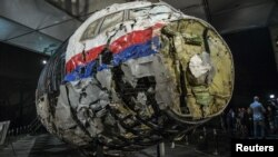 Донбасс аспанында апатқа ұшыраған ұшақтың жерден табылған сынықтарынан қайтадан құрастырылған фюзеляж бөлігі. Нидерланд, 2015 жылдың соңында түсірілген сурет.