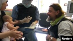Сирийский активист и местная жительница беседуют с инспектором ООН, который расследует химическую атаку в предместье Дамаска