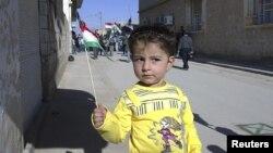 Сирија, девојче држи во рака курдско знаме за време на антивладините протести