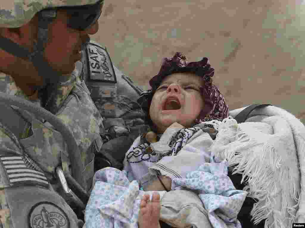 Американський військовий тримає на руках хвору афганську дівчинку, провінція Кандагар, Афганістан, 19 вересня.Photo by Oleg Popov for Reuters