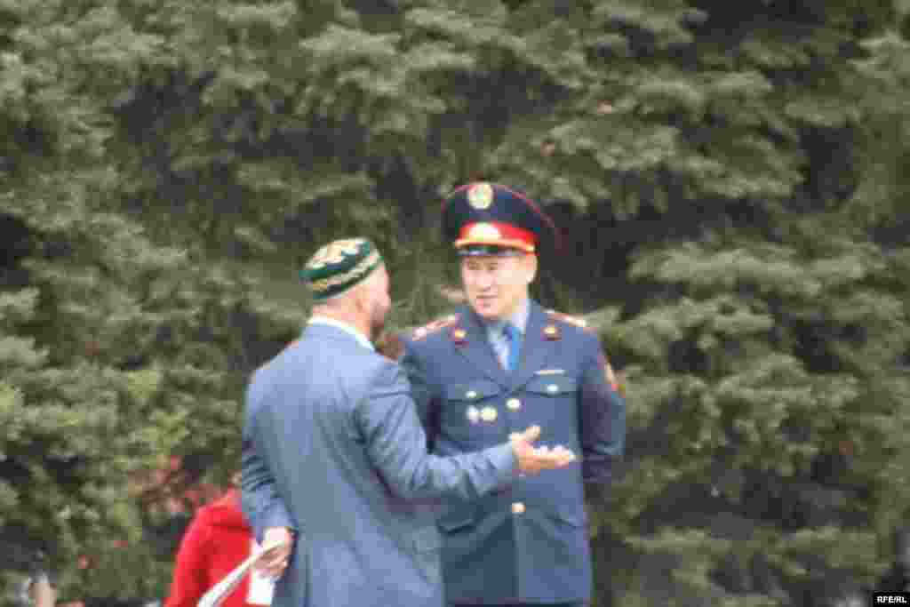 Человек в штатском беседует с офицером казахской полиции после чтения оппозиционной газеты. Алматы, 1 мая 2010 года.